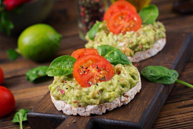 cafe da manha saudavel sanduiche de pao torrado com guacamole e tomate em uma mesa de madeira 2829 5057