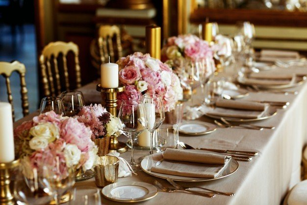 mesa longa servida com louca de porcelana e talheres brilhantes servidos com flores de cor de rosa 1304 3701