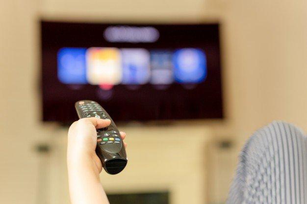mao usando o controle remoto para assistir televisao em casa 42667 1357